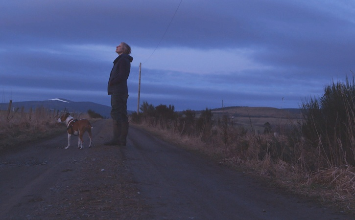 A woman stands on a country road at twilight, looking off into the distance, with a dog at her feet and snow-topped hills in the distance.